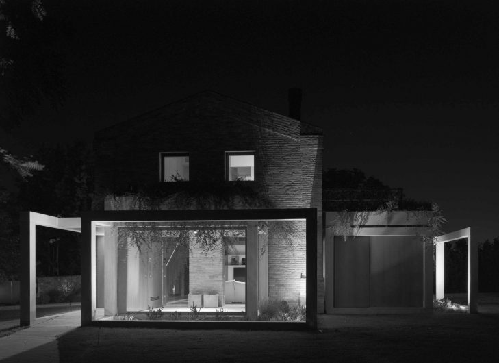 Black and white image of the façade of Villa Parma with fixed glass in the foreground