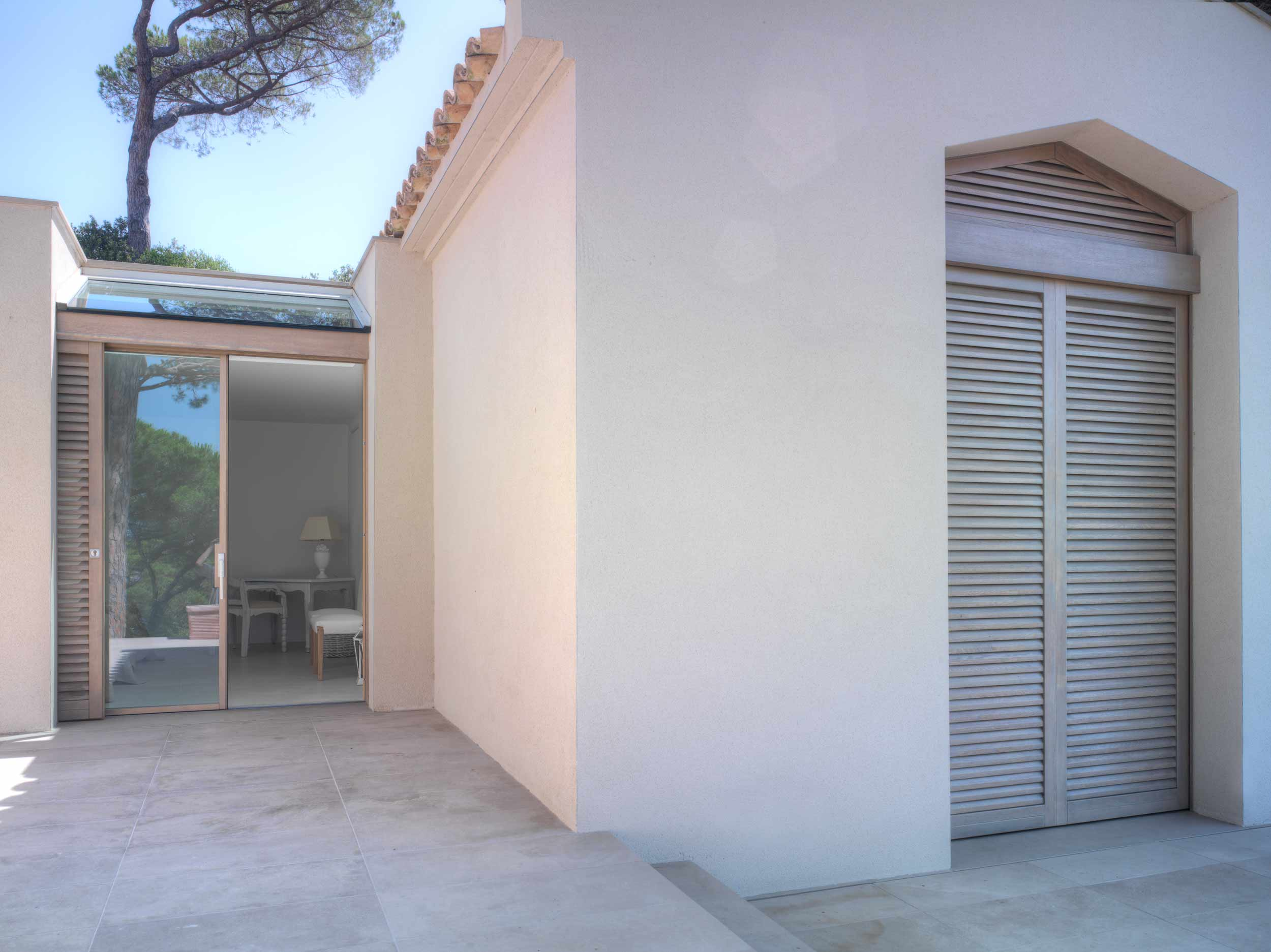 View of the facade of the villa with wooden shutters