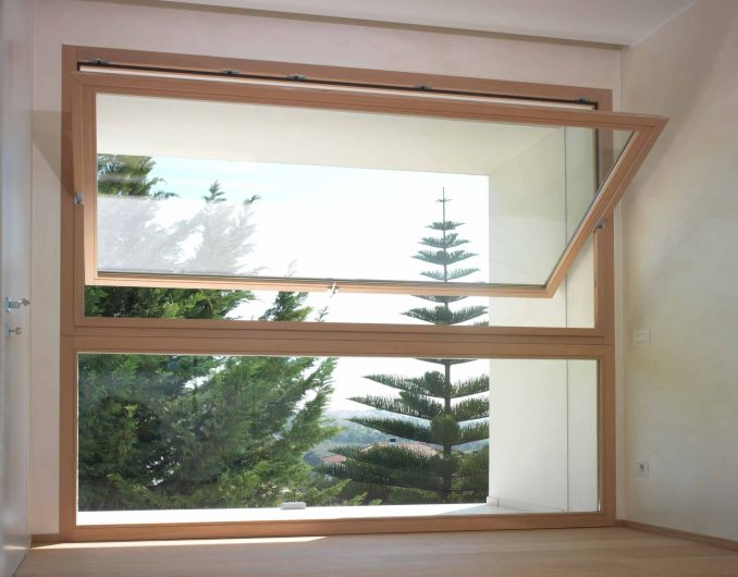Front view of a wooden hinged window with a natural finish