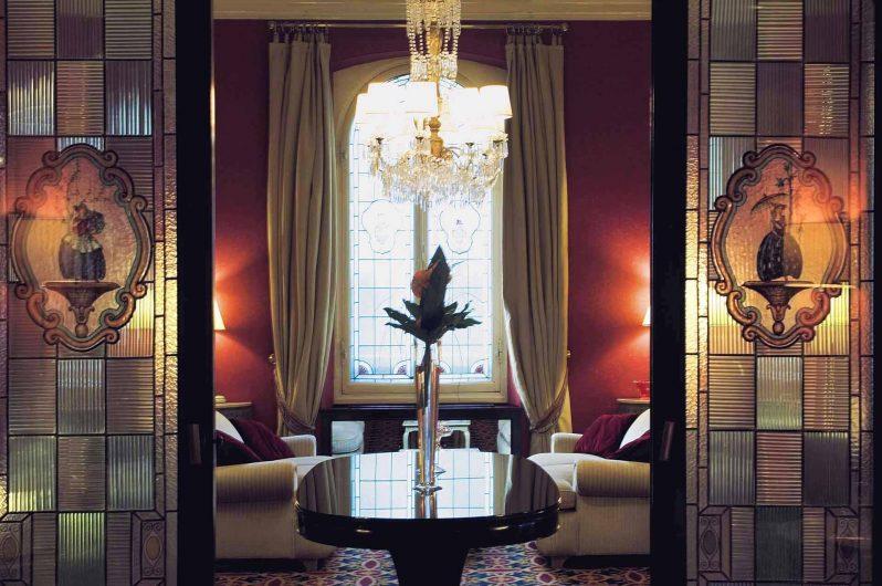 Dettaglio della zona soggiorno con finestra a due ante in legno laccato bianco dal profilo classico