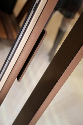 Detail of the handle of a lift and slide covered in brushed bronze aluminium