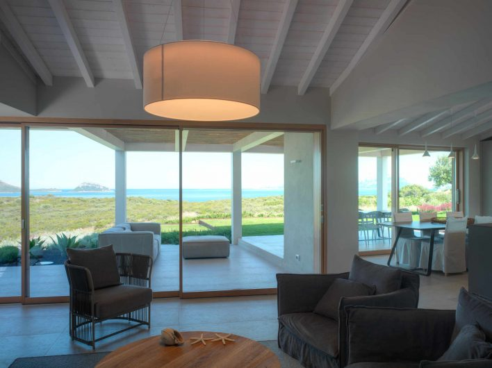 View of the living room of Villa Costa Smeralda with two sliding doors on the back wall