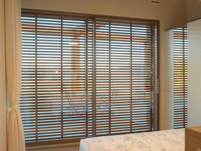 Lift and slide of the bedroom with closed wooden slatted sunshades