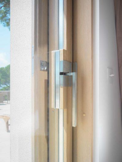 Detail of the custom satin chrome handle of the sliding door