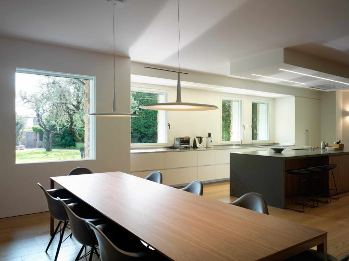 View of the kitchen and dining area with fixed and flush-to-the-wall white lacquered windows